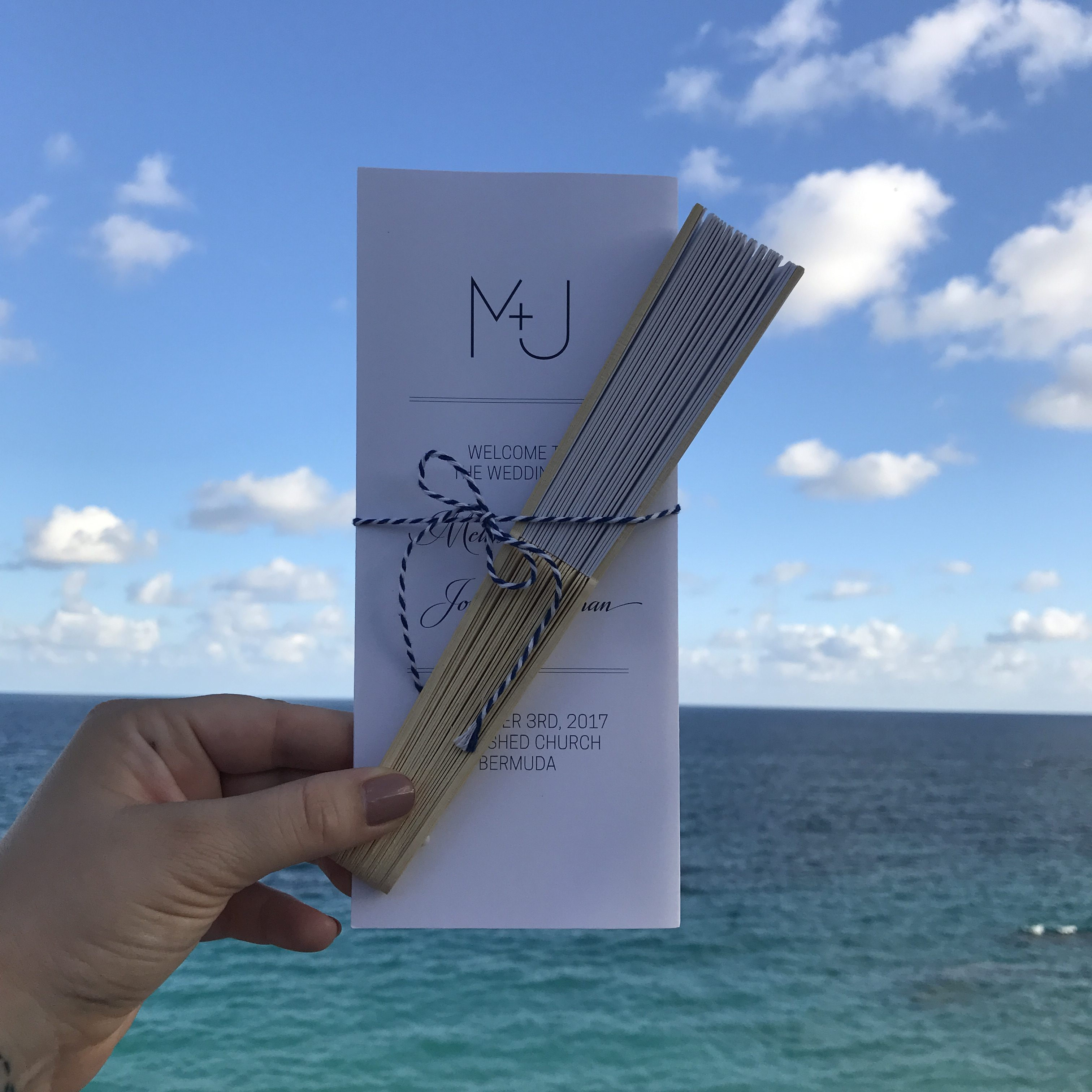 A hand holds a wedding program with a fan and custom branding in front of the ocean.