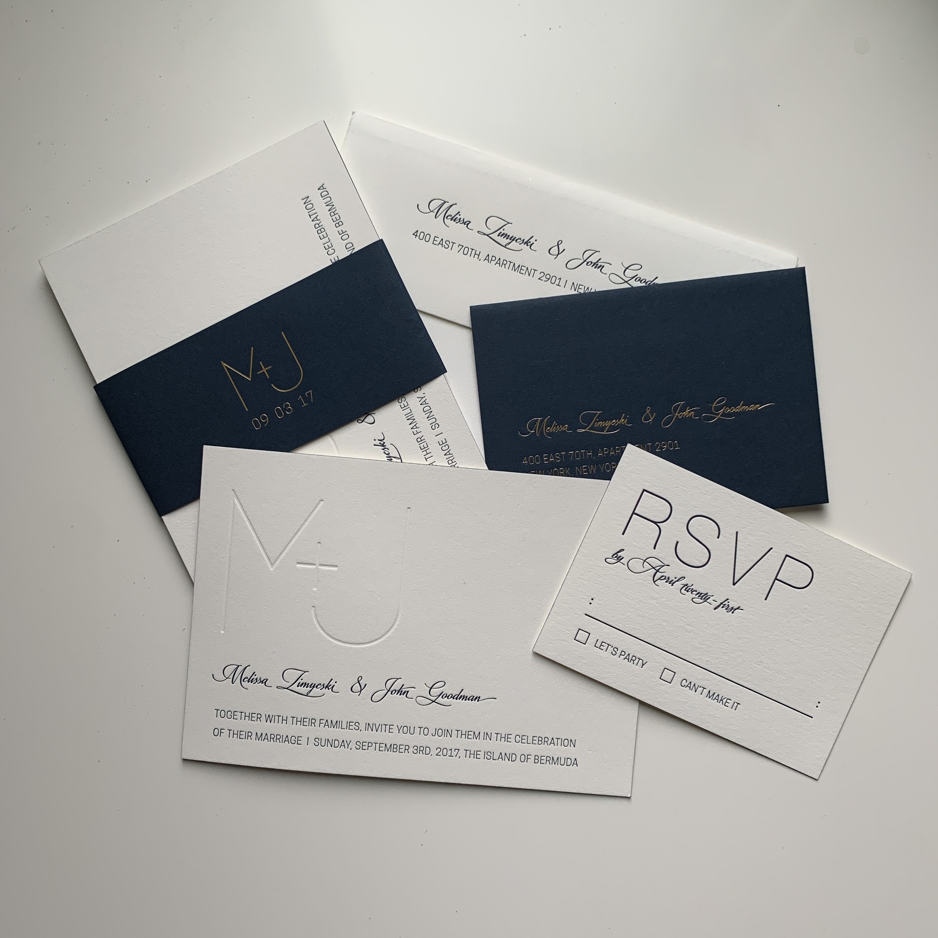 A wedding invite suite with M+J branding in white, navy and gold. Invite, RSVP, RSVP Envelope, Belly band, Printed envelope.