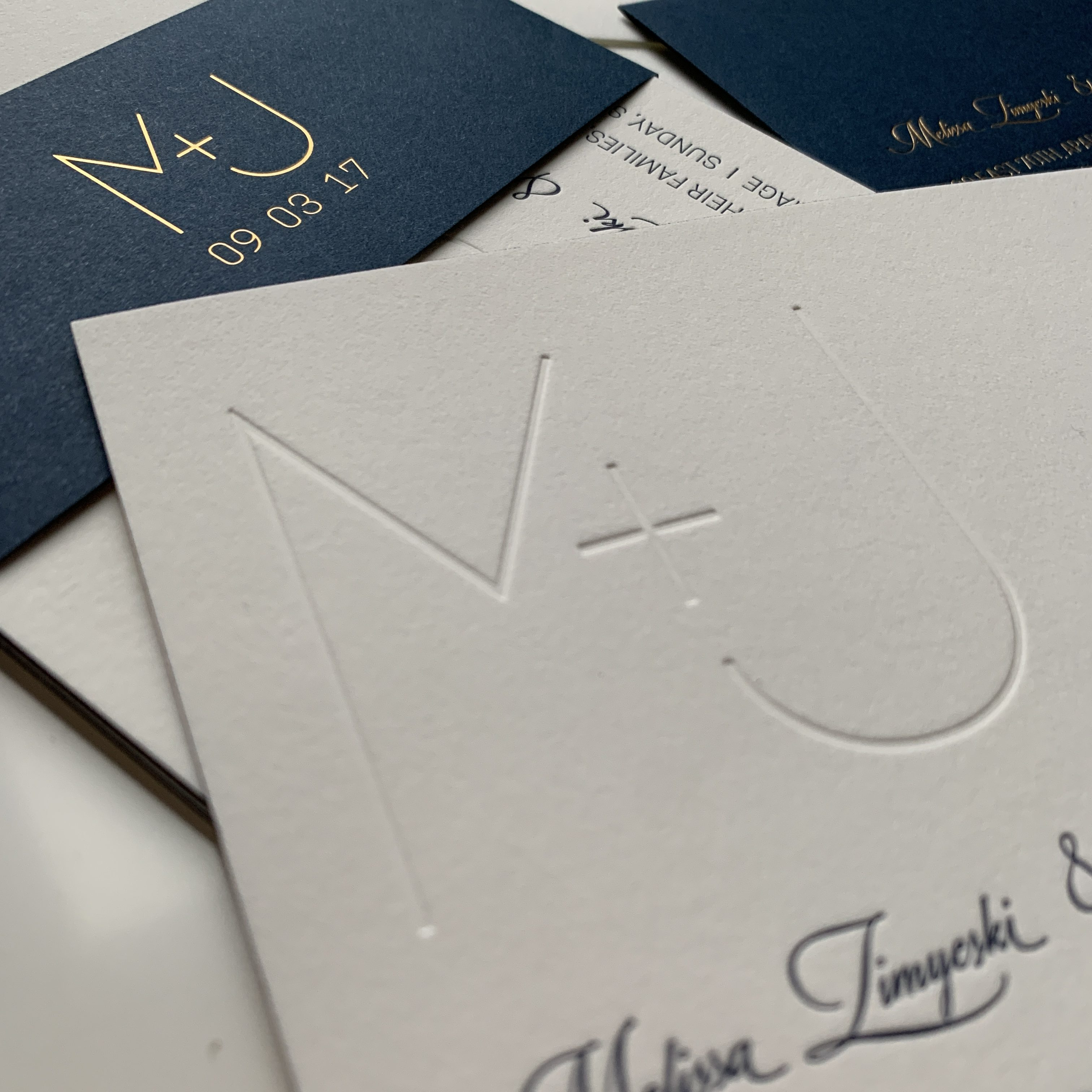 Close up detail of M+J branding and invites. Blind emboss printing on white and gold foil letterpress printing on navy are shown.