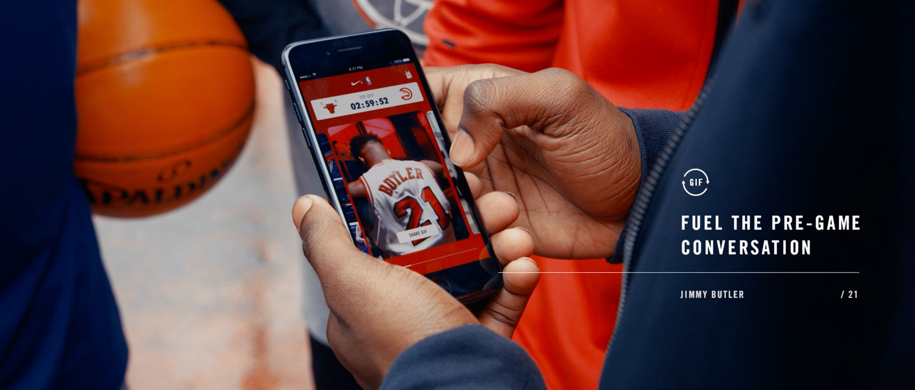 A young man is holding a phone with the Nike Connected Jersey experience showing.